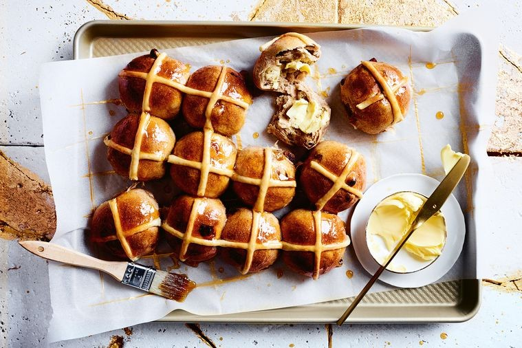 Hot cross buns on a tray with baking paper and butter in a white dish and brush for oil and gold butter knife
