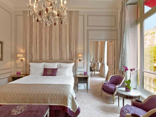 beautiful luxury hotel room in Paris with large white bed, rod pillows, a secured background and white walls