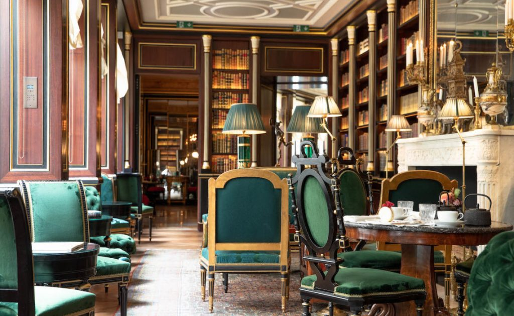 Green velvet chairs in ruch wooden room with large book shelves, filled with books and natural light