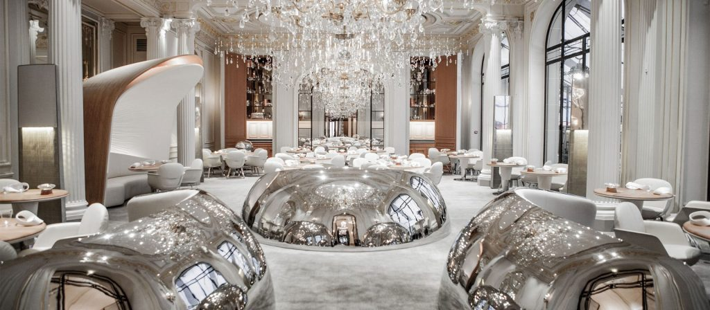 Luxe resaturant with silver domes and huge chandaliers with white carpet