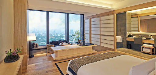 Minimalist hotel room in Tokyo japan with nedlooking out over 3 windows