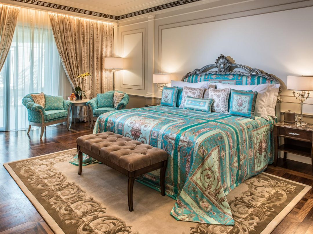 Magnificant hotel suite with versace green and brown satin bed cover, brown stool at end and heavy curtains