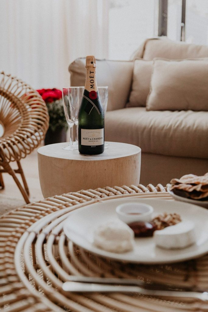 champagne and cheese platter in well lit apartment style room