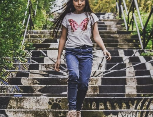 teenager girl with long dark hair walking down grey stairs with white t-shirt with pink butterfly on it