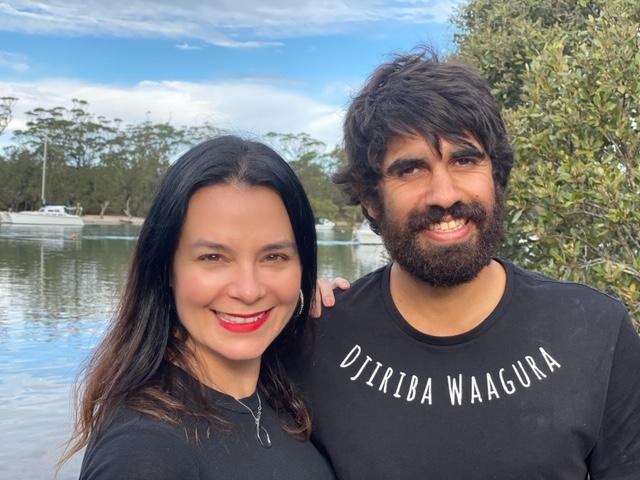 brunette white woman with aboriginal, Australian native man both in black t-shirts