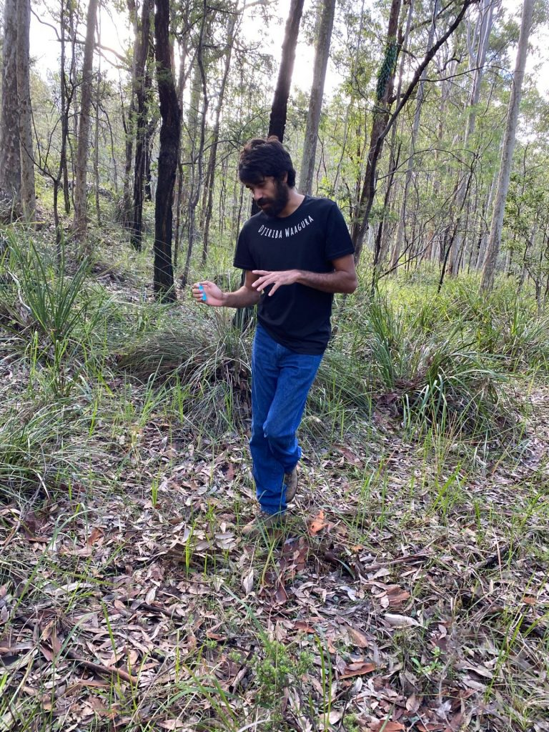 aboriginal man with black t-shirt and blue jeans in Australian bush