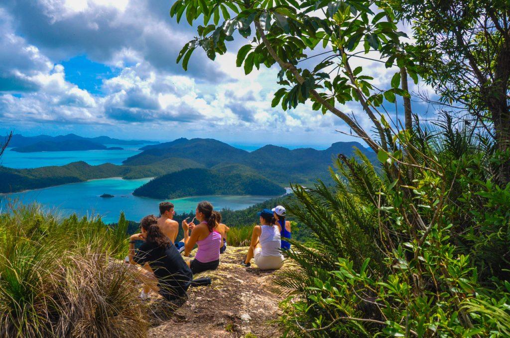 Family sitting on hill overlookig water in australia