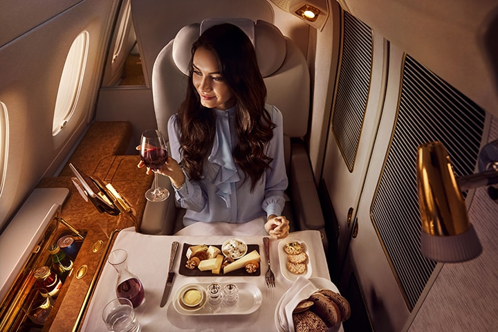 woman in first class with meal tray in front of her