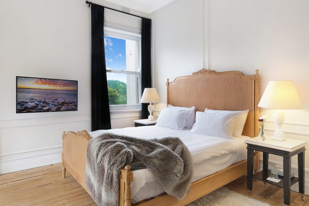 Bwautiful wooden bed frame with white mattress and grey throw rug