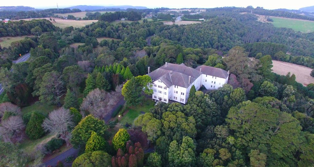 The gracious manor house is surrounded by huge trees and a sprawling, manicured garden.