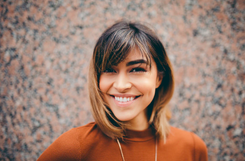 Female smiling with glowing, youthful skin.