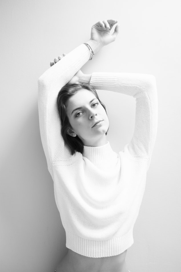 back and white image of women in cream jumper with hands in the air leaning against a wall