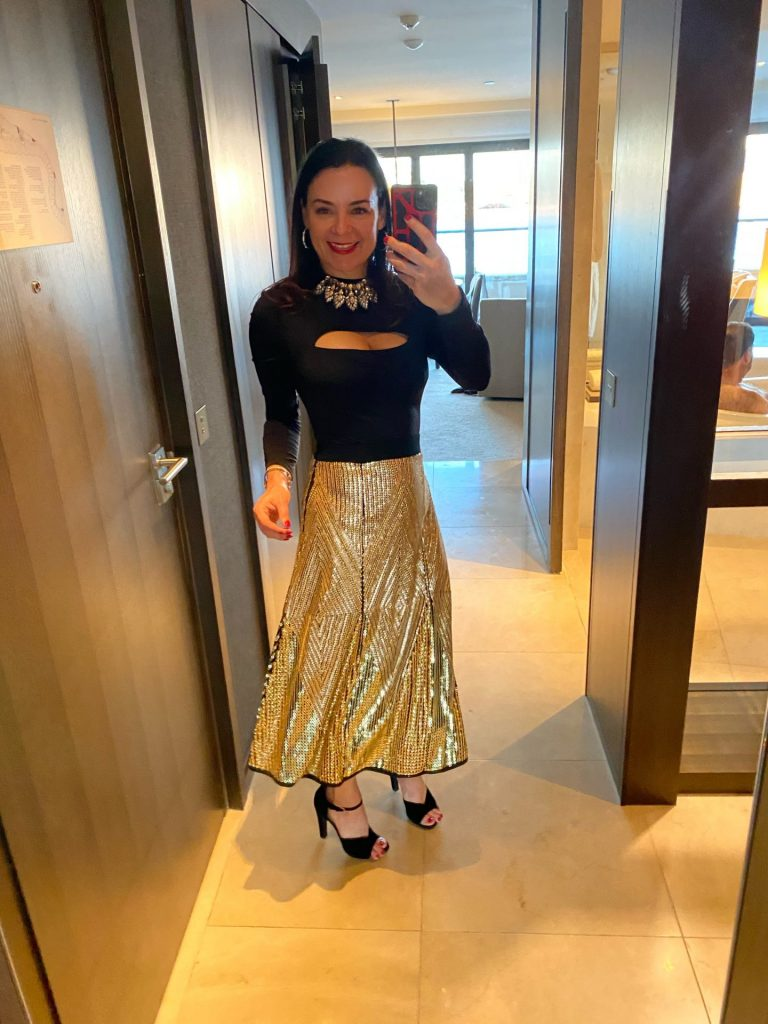 woman in gold skirt and black top
